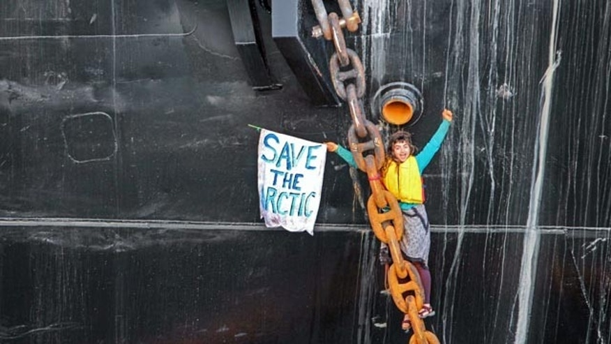 May 22, 2015: A woman identified as Chiara DAngelo hangs in a climbing harness from the anchor chain of the Royal Dutch Shell support ship Arctic Challenger in the harbor at Bellingham, Wash. (Reese Semanko via AP)