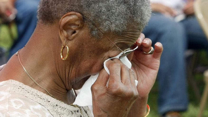Shirley Reid cries during a memorial service at Galilee Memorial Gardens cemetery Monday, May 25, 2015, in Memphis, Tenn. The cemetery was opened to visitors on Memorial Day after being closed after the cemetery owner was accused of burying multiple bodies in single graves by crushing and stacking caskets. (AP Photo/Karen Pulfer Focht)