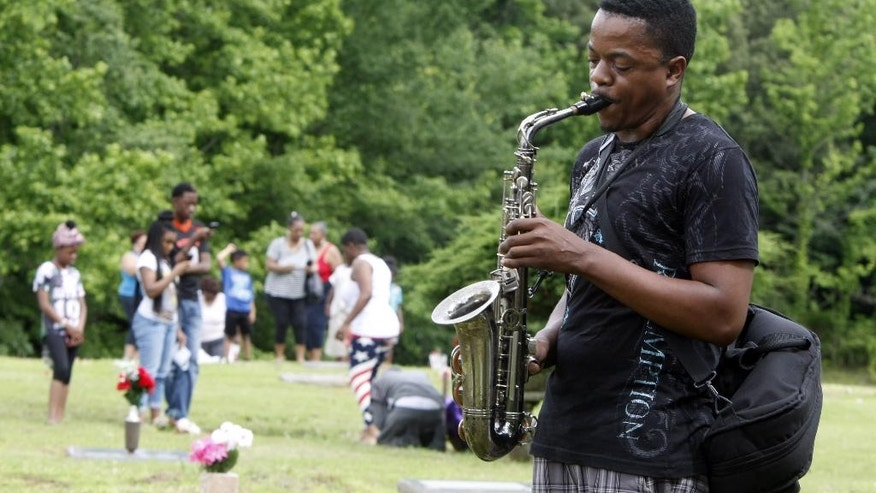 "Darnell Bonner plays ""Amazing Grace"" during a memorial ceremony at Galilee Memorial Gardens cemetery Monday, May 25, 2015, in Memphis, Tenn. The cemetery was opened to visitors on Memorial Day after being closed after the cemetery owner was accused of burying multiple bodies in single graves by crushing and stacking caskets. (AP Photo/Karen Pulfer Focht)"