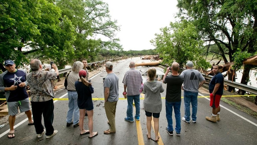People look at the Hwy 12 bridge over the Blanco River in Wimberley, Texas, which was blocked by several large trees after a flood on Sunday May 24, 2015. (Jay Janner/Austin American-Statesman via AP) AUSTIN CHRONICLE OUT, COMMUNITY IMPACT OUT, INTERNET AND TV MUST CREDIT PHOTOGRAPHER AND STATESMAN.COM, MAGS OUT