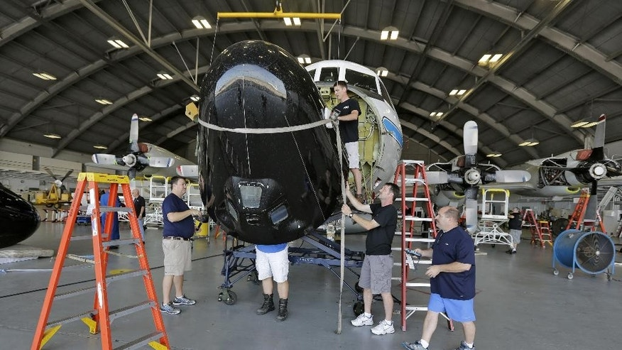 "Technicians remove the forward radar cover of the National Oceanic and Atmospheric Administration's P-3 turboprop aircraft ""Miss Piggy"" Friday, May 15, 2015, at MacDill Air Force Base in Tampa, Fla. While best known as ""hurricane hunters,"" NOAA's four-engine WP-3D turboprops support a wide variety of national and international meteorological, oceanographic, and environmental research and monitoring programs in addition to hurricane research and reconnaissance. Projects range from air chemistry, climate, and ocean heat content studies to satellite data validation. (AP Photo/Chris O'Meara)"