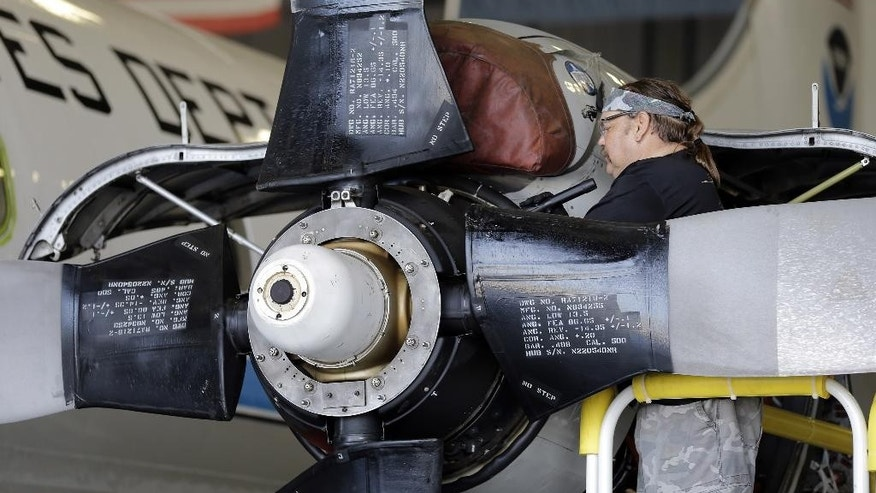 "Technician Joseph Klippel works on the engines on the National Oceanic and Atmospheric Administration's P-3 turboprop aircraft ""Miss Piggy"" Friday, May 15, 2015, at MacDill Air Force Base in Tampa, Fla. While best known as ""hurricane hunters,"" NOAA's four-engine WP-3D turboprops support a wide variety of national and international meteorological, oceanographic, and environmental research and monitoring programs in addition to hurricane research and reconnaissance. Projects range from air chemistry, climate, and ocean heat content studies to satellite data validation. (AP Photo/Chris O'Meara)"