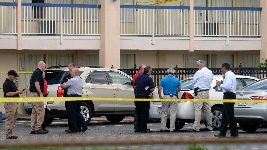 Law enforcement officials investigate after a shooting at the Days Inn motel in Bossier City, La., Tuesday, May 26, 2015. Authorities say a 9-year-old Texas kidnap victim has been safely recovered but an FBI agent and a suspect in the case were shot when gunfire broke out at the northwest Louisiana motel. (Douglas Collier/The Shreveport Times via AP) MAGS OUT; MANDATORY CREDIT SHREVEPORTTIMES.COM;  NO SALES