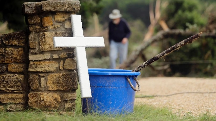 A cross stands at the driveway to a vacation home that was swept down the swollen Blanco River, Tuesday, May 26, 2015, in Wimberley, Texas. Authorities say recovery teams  will resume looking for as many as a dozen missing people, in an area where punishing rains have destroyed or damaged more than 1,000 homes and killed at least three people statewide this weekend. (AP Photo/Eric Gay)