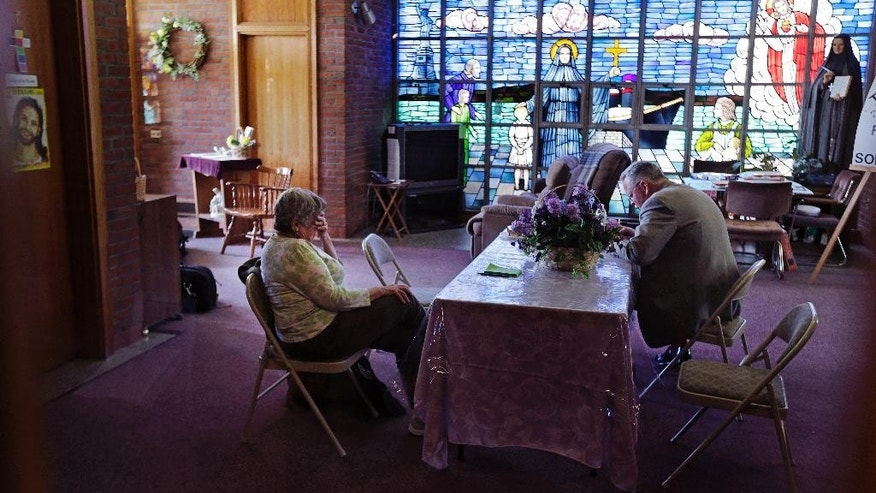 Barbara Nappa, of Scituate, Mass., left, sits with Jon Rogers during a vigil at the St. Frances Xavier Cabrini Church in Scituate, Mass., Wednesday, May 20, 2015.  Parishioners occupying a closed Catholic church for nearly 11 years may be at their end. A state judge has ordered the Friends of St. Frances X. Cabrini, which has occupied the church day and night since October 2004, to vacate by May 29. (AP Photo/Charles Krupa)