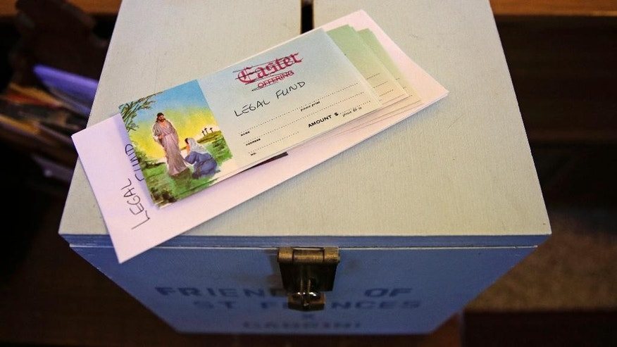 A makeshift donation envelope for a legal fund, with the wording of Easter offering crossed out, sits atop of a collection box at the St. Frances Xavier Cabrini Church in Scituate, Mass., Wednesday, May 20, 2015.  Parishioners occupying a closed Catholic church for nearly 11 years may be at their end. A state judge has ordered the Friends of St. Frances X. Cabrini, which has occupied the church day and night since October 2004, to vacate by May 29. (AP Photo/Charles Krupa)