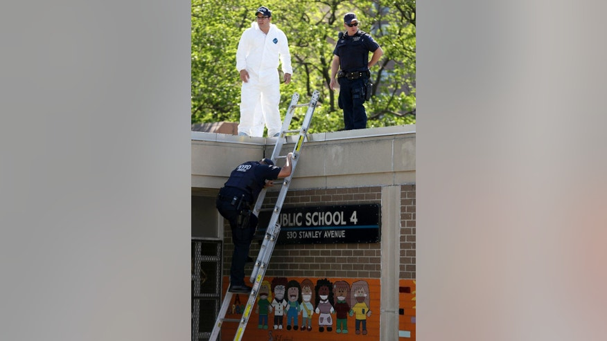 Police officers climb off the top of a public school during an investigation into a shooting in Brooklyn's East New York section, New York, Tuesday, May 26, 2015. The New York Police Department says a man suspected of killing his ex-girlfriend outside a casino has been shot to death by police. (AP Photo/Seth Wenig)