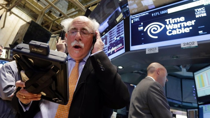Trader Peter Tuchman, left, works the post that handles Time Warner Cable on the floor of the New York Stock Exchange, Tuesday, May 26, 2015.  Charter Communications is buying Time Warner Cable for $55.33 billion, creating another U.S. TV and Internet giant. (AP Photo/Richard Drew)