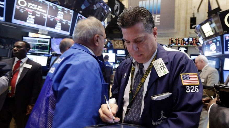 Trader William McInerney, right, works on the floor of the New York Stock Exchange, Tuesday, May 26, 2015. Stocks are opening lower on Wall Street as traders return from the Memorial Day holiday in the U.S.(AP Photo/Richard Drew)
