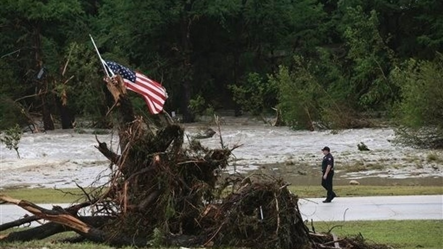 Hays County Precinct 4 Deputy Constable John Ellen patrols River Road at the 7A Resort in Wimberley, Texas, Monday, May 25, 2015. Heavy rains led to historical floods along the Blanco River in Wimberley. (Jerry Lara/The San Antonio Express-News via AP)