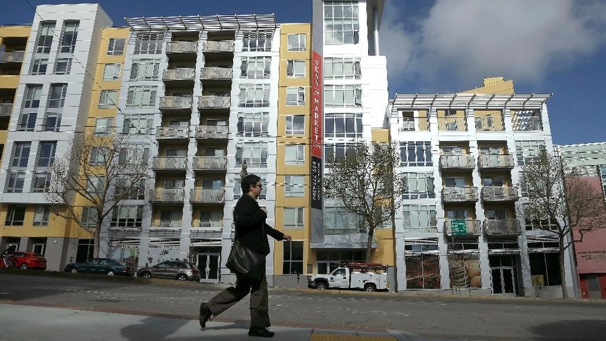 FILE - In this Monday, March 17, 2014, file photo, a woman walks across the street from the Venn on Market apartment and condominium building in San Francisco. U.S. home prices rose at a steady pace in March, pushed higher by a limited supply of houses for sale, according to the Standard & Poor's/Case-Shiller 20-city home price index released Tuesday, May 26, 2015. (AP Photo/Jeff Chiu, File)