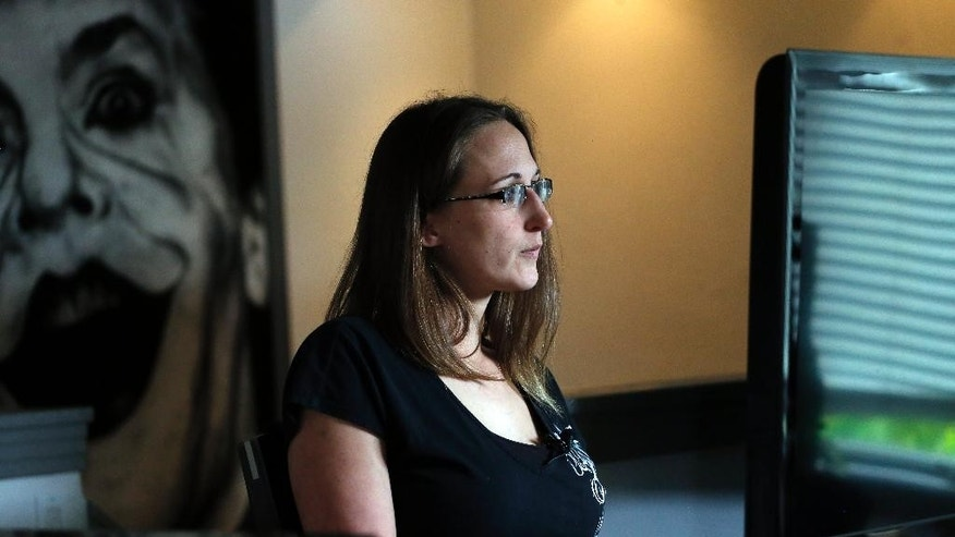 In this May 21, 2015 photo, Christina Blache sits in her living room during an interview with The Associated Press, in Northglenn, Colo. Blache, who was shot through both legs with an assault rifle when James Holmes opened fire in a packed movie theater in Aurora, Colo., in 2012, says that testifying in the Holmes trial has been both cathartic and re-traumatizing. (AP Photo/Brennan Linsley)