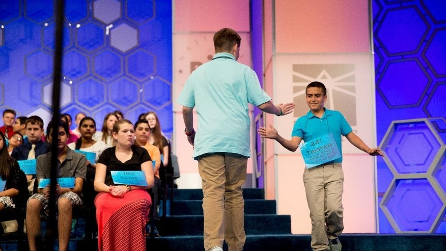 "Grant Taylor, 12, of Lubbock, Texas, left, is congratulated by Tristan Salinas, 13, of McAllen, Texas, as he correctly spelled ""wanton"" during the 2015 Scripps National Spelling Bee, Wednesday, May 27, 2015, in Oxon Hill, Md. (AP Photo/Andrew Harnik)"