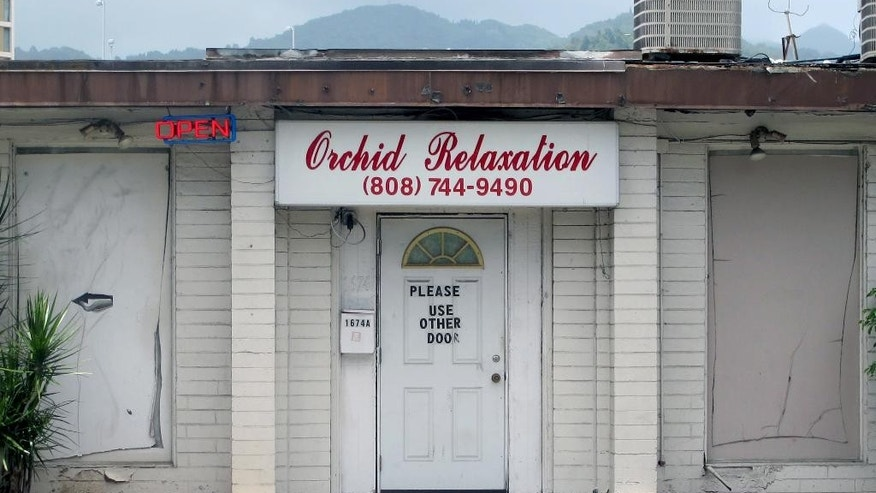 FILE - This May 6, 2015 file photo shows an open sign hanging outside Orchid Relaxation in Honolulu. The massage parlor was one of several local businesses that were targeted in a police prostitution sting. Honolulu's top prosecutor is dismissing sex assault charges against 16 women arrested in the massage parlor prostitution sting. Prosecuting Attorney Keith Kaneshiro said Wednesday, May 27, the allegations might have constituted a technical violation of law, but proof beyond a reasonable doubt couldn't be established. (AP Photo/Jennifer Sinco Kelleher,File)