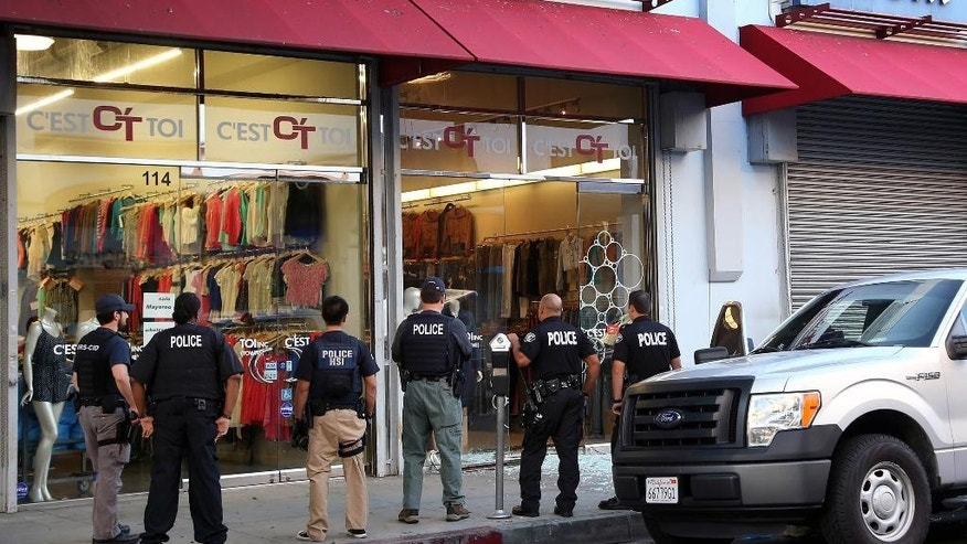 FILE - In this Wednesday, Sept. 10, 2014, file photo, law enforcement agents stand outside a clothing store after a raid in the Los Angeles fashion district. A father and son have agreed to plead guilty to crimes stemming from an investigation into suspected money laundering for Mexican drug cartels in the Los Angeles fashion district. Xilin Chen and his son, Tom Chen, signed plea agreements in federal court in Los Angeles this week, and a judge is expected to accept the agreements at a hearing Friday, May 29, 2015. (AP Photo/ Nick Ut, File)