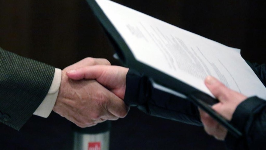 In this April 22, 2015 photo, Ralph Logan, general manager of Microtrain, left, shakes hands with a job seeker during a National Career Fairs job fair in Chicago. The U.S. Labor Department reports on the number of people who applied for unemployment benefits last week on Thursday, May 28, 2015. (AP Photo/M. Spencer Green)