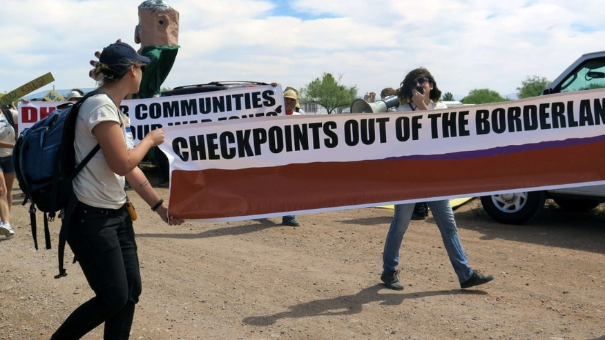 May 27, 2015: Two protesters carry a large banner as they walk toward a U.S. Border Patrol checkpoint on a two-lane road in Amado, Ariz.