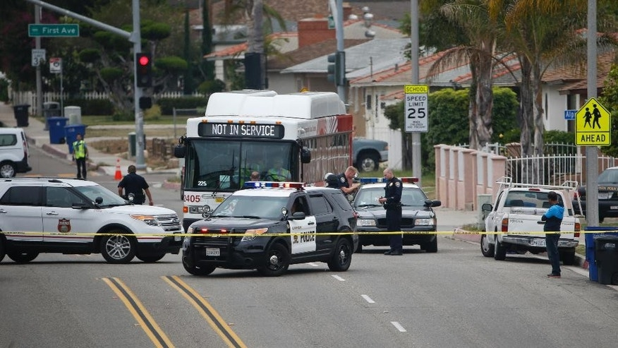 A  bus moves into position as police prepare to evacuate residents of an apartment building where a man is believed to be holed up in his apartment with two children and a woman after a shooting outside the housing complex, Thursday, May 28, 2015, in Chula Vista, Calif. (AP Photo/Lenny Ignelzi)