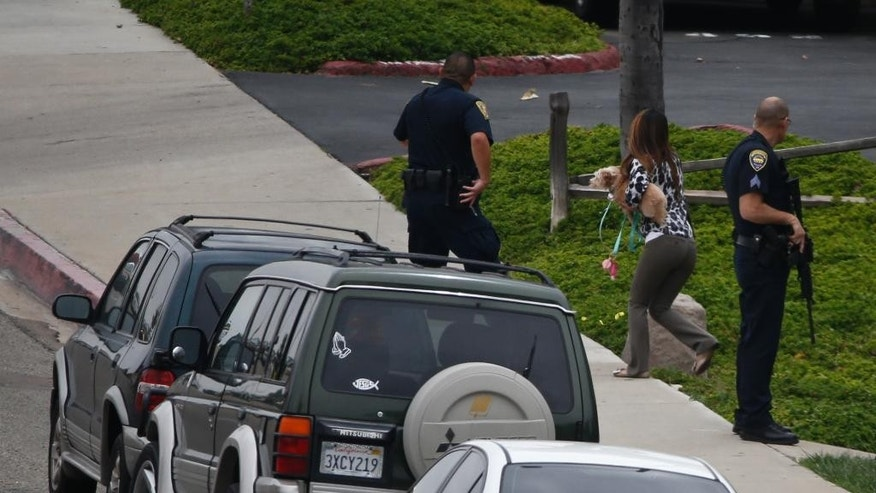 Residents are evacuated from an apartment building where a man is believed to be holed up in his apartment with two children and a woman after a shooting outside the housing complex, Thursday, May 28, 2015, in Chula Vista, Calif. (AP Photo/Lenny Ignelzi)