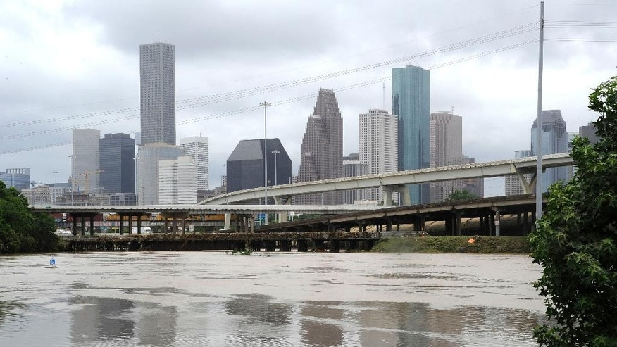 Flood waters overrun the banks of the bayou in downtown Houston, Tuesday, May 26, 2015. Floodwaters kept rising Tuesday across much of Texas as storms dumped almost another foot of rain on the Houston area, stranding hundreds of motorists and inundating the famously congested highways that serve the nation's fourth-largest city.  (AP Photo/Pat Sullivan)