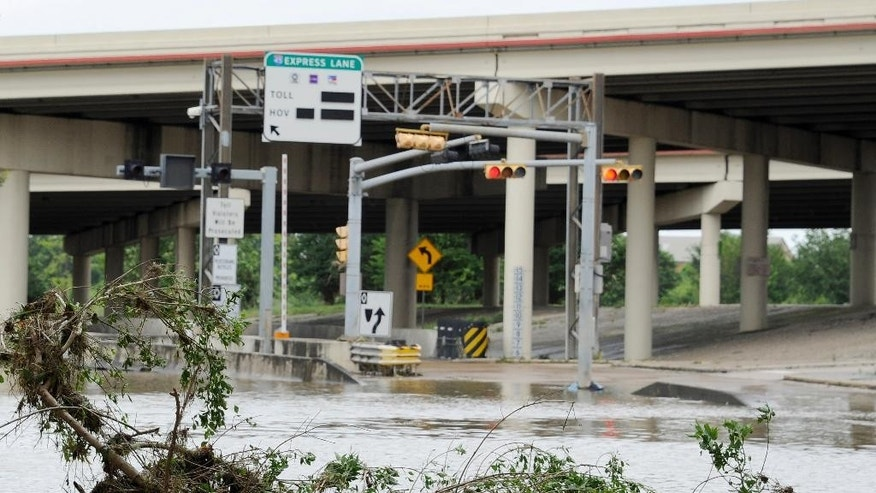 A highway entrance is covered in water and debris after flood waters overran the banks of the bayou in downtown Houston, Tuesday, May 26, 2015. Floodwaters kept rising Tuesday across much of Texas as storms dumped almost another foot of rain on the Houston area, stranding hundreds of motorists and inundating the famously congested highways that serve the nation's fourth-largest city. (AP Photo/Pat Sullivan)