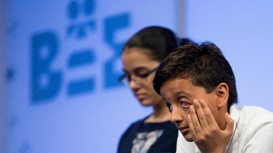 Jairam Hathwar, 12, of Corning, N.Y., right, sits on stage during the semifinals of the Scripps National Spelling Bee, Thursday, May 28, 2015,  in Oxon Hill, Md. (AP Photo/Andrew Harnik)