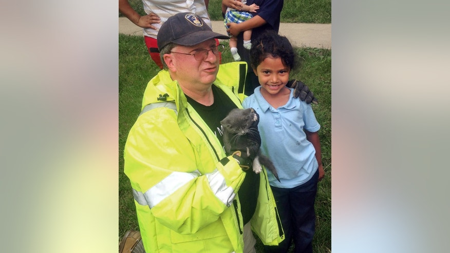 In this May 26, 2015 photo, Lancaster Township Fire Department Deputy Fire Chief  Glenn Usdin, left, holds the kitten that was rescued with the help of 6-year-old Janeysha Cruz in Lancaster, Pa. Firefighters were too big to rescue the kitten from a storm drain, so with the permission of Cruz's mother, they lowered the kindergartner nearly 3 feet into the storm drain to coax the kitten out. (Brett J. Fassnacht/Lancaster Township Fire Department via AP)