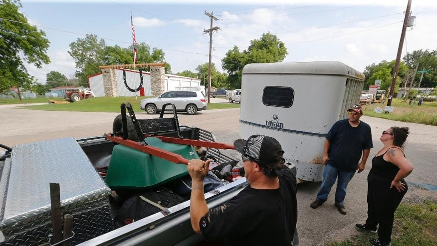 Rhett Pfaffenhauser loads his belongings onto Cheyenne Cobb's truck as he and his friend Deborah Arlin, right, leave Horseshoe Bend, Texas, for safer shelter elsewhere as authorities call for an evacuation of Horseshoe Bend, because the Brazos River is expected to flood, Wednesday, May 27, 2015. (Rodger Mallison/The Fort Worth Star-Telegram via AP) MAGAZINES OUT; (FORT WORTH WEEKLY, 360 WEST) MANDATORY CREDIT