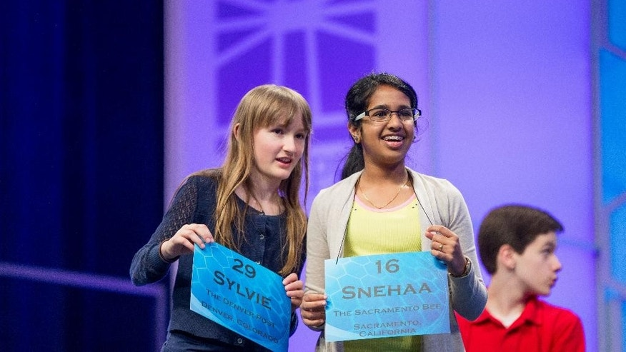 Sylvie Lamontagne, 12, of Denver, left, and Snehaa Ganesh Kumar, 12, of Sacramento, Calif., center, stand on stage during the semifinals of the 2015 Scripps National Spelling Bee, Thursday, May 28, 2015, in Oxon Hill, Md. (AP Photo/Andrew Harnik)