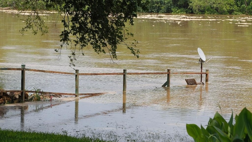 A fence is overtaken by the river as authorities call for an evacuation of Horseshoe Bend, Texas because the Brazos River is expected to flood, Wednesday, May 27, 2015. (Rodger Mallison/The Fort Worth Star-Telegram via AP) MAGAZINES OUT; (FORT WORTH WEEKLY, 360 WEST)