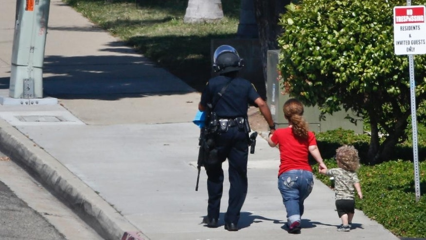 A police officer leads the wife of a gunman and a child to safety during a day-long standoff that authorities said began when the suspect killed a neighbor hours earlier, Thursday, May 28, 2015, in Chula Vista, Calif. (AP Photo/Lenny Ignelzi)