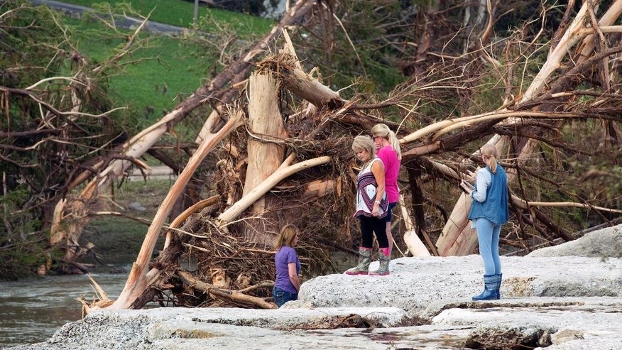 From left to right, Cara Hewitt, Linda Balas, Kathy Bullard and Doreen Crow look at the spot in Wimberley, Texas, on Thursday May 28, 2015, where eight of their friends from Corpus Christi were swept away in a flood. (Jay Janner/Austin American-Statesman via AP)  AUSTIN CHRONICLE OUT, COMMUNITY IMPACT OUT, INTERNET AND TV MUST CREDIT PHOTOGRAPHER AND STATESMAN.COM, MAGAZINES OUT