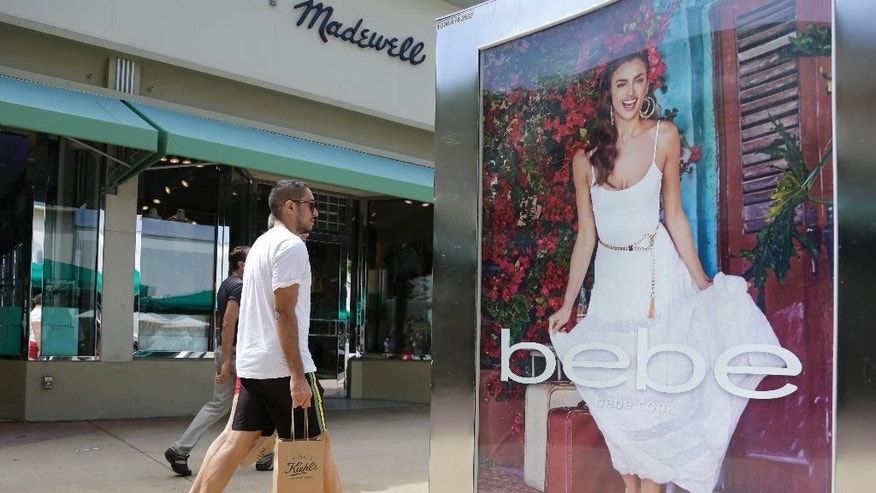 "FILE - In this March 13, 2015 file photo, shoppers walk past an advertisement for retailer ""bebe"" along Lincoln Road Mall, a pedestrian street featuring retail stores and outdoor cafes, in Miami Beach, Fla. The University of Michigan issues its monthly index of consumer sentiment for May on Friday, May 29, 2015. (AP Photo/Lynne Sladky, File)"