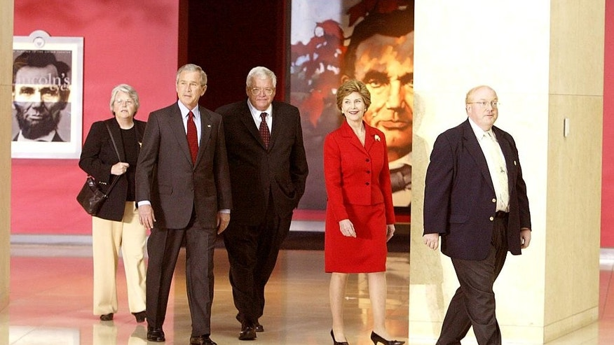 "In this April 20, 2005 file photo, House Speaker Dennis Hastert, center, tours the new Abraham Lincoln Presidential Museum in Springfield, Ill. with President George W. Bush and First Lady Laura Bush and museum director Richard Norton Smith, right. At left is Hastert's wife, Jean. A newly unveiled indictment against Hastert released Thursday, May 28, 2015, accuses the Republican of agreeing to pay $3.5 million in hush money to keep a person from the town where he was a longtime schoolteacher silent about ""prior misconduct."" (File/The State Journal-Register via AP)"