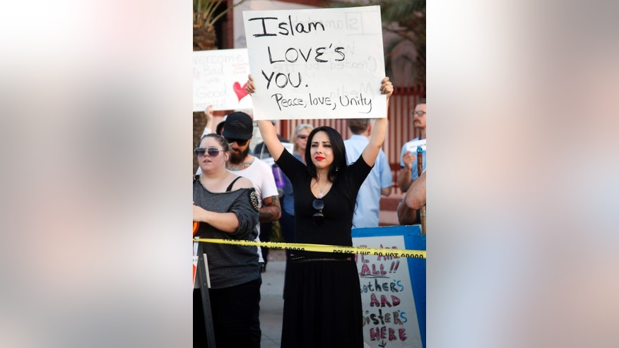 Protesters gather outside the Islamic Community Center of Phoenix, Friday, May 29, 2015. About 500 protesters gathered outside the Phoenix mosque on Friday as police kept two groups sparring about Islam far apart from each other.(AP Photo/Rick Scuteri)