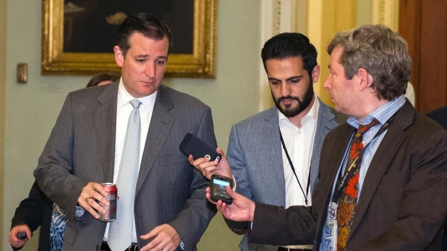 Sen. Ted Cruz., R-Texas., left, speaks with reporters as he walks to the Senate Chamber for a special session of the Senate to extend surveillance programs,  in Washington, Sunday, May 31, 2015. Senate Republicans say they've been unable to make a deal to extend contested anti-terror provisions. As a result, the post-Sept. 11 programs will expire at midnight.  (AP Photo/Cliff Owen)
