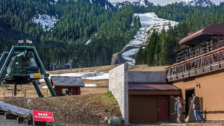 In this photo taken March 13, 2015, a solitary skier walks past maintenance worker Thomas Wieman, right, as he cleans up at Crystal Mountain ski resort near Greenwater, Wash. A lack of snow brought Crystal one of the worst ski seasons in Western Washington's history, and farmers, growers and wildlife managers in Washington state are preparing for the worst drought in a decade as the summer approaches. (Dean J. Koepfler/The News Tribune via AP)