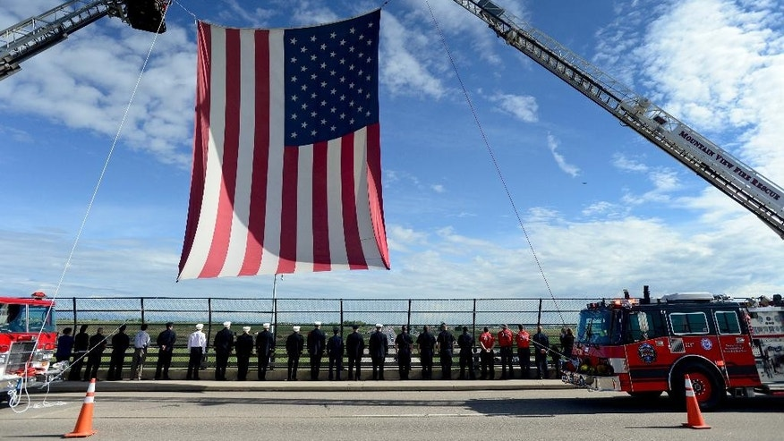 Firefighters from Mountain View Fire Rescue and Frederick Firestone Protection District stand at attention as the Colorado State Patrol procession for cadet 21-year-old Taylor Thyfault passes Highway 52 in Erie, Colo., on Friday, May 29, 2015. Thyfault was hit and killed May 23 by a driver allegedly fleeing a traffic stop.  (Matthew Jonas/The Daily Times Call via AP) NO SALES; MANDATORY CREDIT