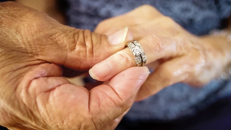 Robert Kirker puts a wedding ring, lost for 30 years, on his wife Ofelia's hand at their home in Las Cruces, N.M., May 27, 2015. It's been decades since Ofelia Kirker lost her wedding rings, but she'll be wearing the treasured jewelry for her 64th wedding anniversary. The rings were unearthed in a yard there years ago and have finally made their way back to her thanks to an observant yard worker, one woman's sharp memory and her daughter's persistence. (Jett Lowe/Las Cruces Sun-News via AP) MANDATORY CREDIT