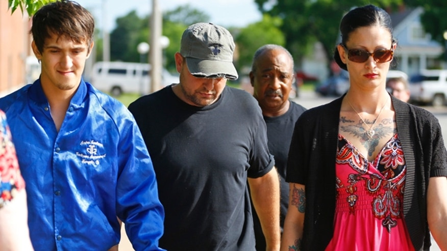 June 1, 2015: Brandon Fischer, center,  walks from the Okmulgee County Jail in Okmulgee, Okla., surrounded by people attempting to shield him from the media.   (AP Photo/Sue Ogrocki)