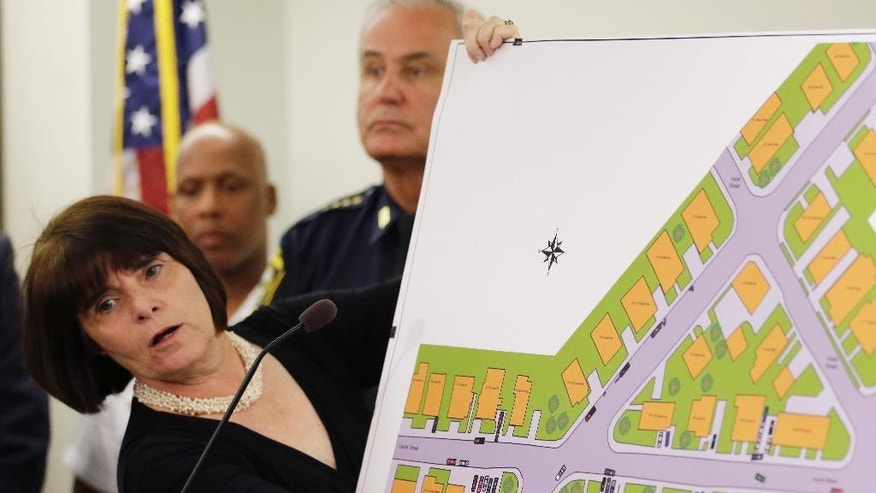 """Middlesex District Attorney Marian Ryan points to a map during a news conference in Woburn, Mass., Tuesday, June 2, 2015, to the spot where a gun battle with the Boston Marathon bombers took place in Watertown, Mass., in April 2013. A report on the incident said it is """"high likely""""  transit police officer Richard Donohue was critically injured by friendly fire during the gun battle. Standing, at center, is Watertown Police Chief Edward Deveau. (AP Photo/Steven Senne)"""