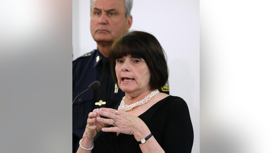 "Middlesex District Attorney Marian Ryan speaks during a news conference Tuesday, June 2, 2015, in Woburn, Mass. A report on a gun battle with the Boston Marathon bombers that took place in Watertown, Mass., in April 2013, said it is ""high likely""  transit police officer Richard Donohue was critically injured by friendly fire during the gun battle. Standing, at center, is Watertown Police Chief Edward Deveau. (AP Photo/Steven Senne)"