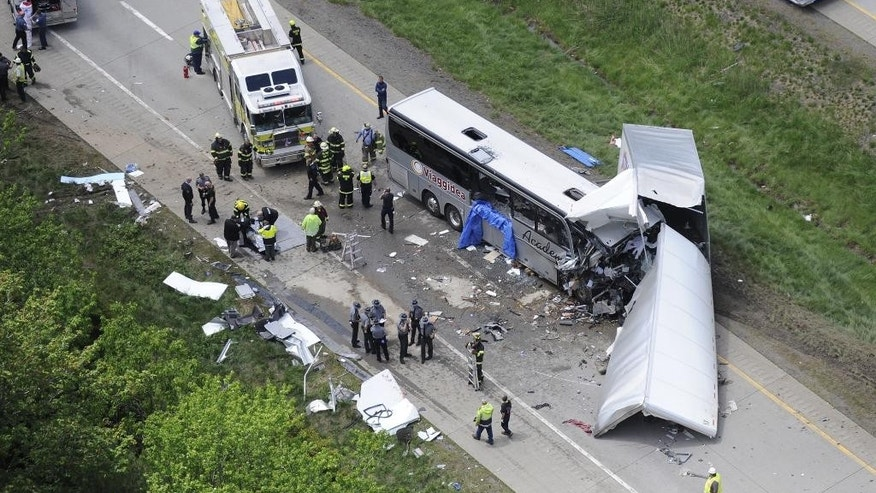 Authorities investigate the scene of a fatal collision between a tractor-trailer and a tour bus on Interstate 380 near Mount Pocono, Pa. Wednesday, June 3, 2015. Multiple people were killed more than a dozen were sent to hospitals. (AP Photo/David Kidwell)