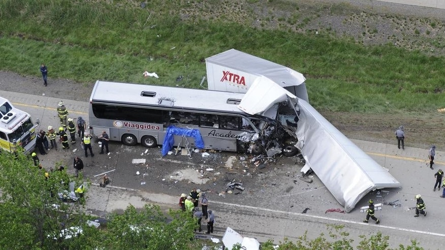 Authorities investigate the scene of a fatal collision between a tractor-trailer and a tour bus on Interstate 380 near Mount Pocono, Pa., Wednesday, June 3, 2015. Multiple people were killed and more than a dozen were sent to hospitals. (AP Photo/David Kidwell)