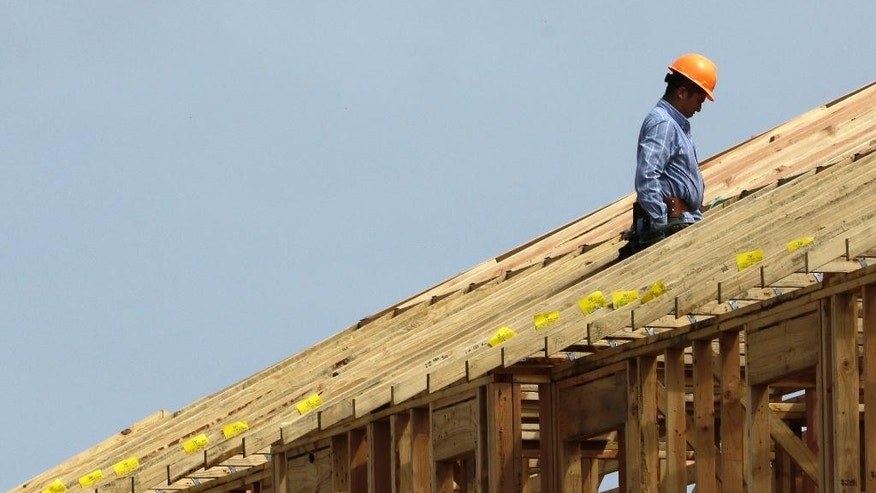 In this March 19, 2015, photo, a construction worker pauses while working on the roof of an apartment complex being built in Spring, Texas. The Federal Reserve releases its latest 'Beige Book' survey of economic conditions on Wednesday, June 3, 2015. (AP Photo/David J. Phillip)
