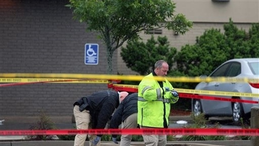 Boston police officers and detectives investigate the scene of a shooting Tuesday, June 2, 2015, in Roslindale, Mass. A man who was under 24-hour surveillance by terrorism investigators was shot and killed after he lunged with a knife at a police officer and an FBI agent outside a pharmacy, authorities said. (Mark Garfinkel/The Boston Herald via AP)  BOSTON GLOBE OUT; METRO BOSTON OUT; MAGS OUT; ONLINE OUT