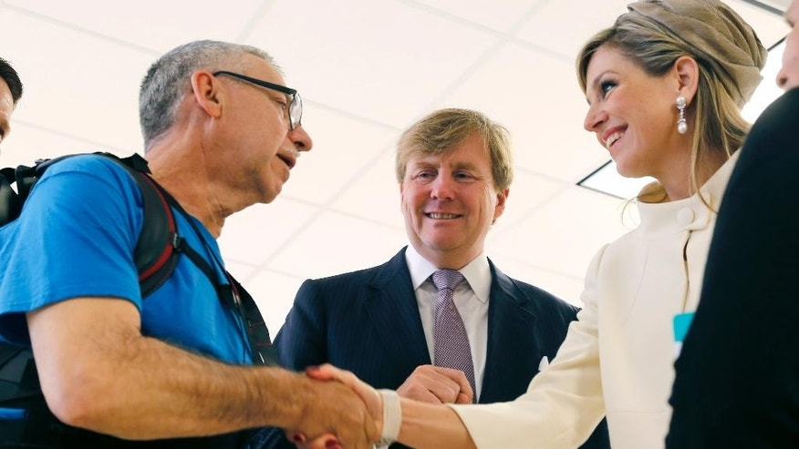 Queen Maxima of the Netherlands, right, shakes hands with Fidel Carabez, as King Willem-Alexander smiles, after a demonstration of Carabez's robotic exoskeleton body suit during the King and Queen's visit to the Rehabilitation Institute of Chicago Wednesday, June 3, 2015, in Chicago. (AP Photo/Christian K. Lee)
