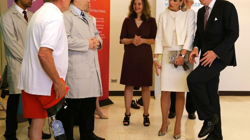 King Willem-Alexander and Queen Maxima of the Netherlands, right, talks to Terry Karpowicz, left, and a staff members at the Rehabilitation Institute of Chicago how Karpowicz's robotic leg functions during a visit by the monarchs Wednesday, June 3, 2015, in Chicago. (AP Photo/Christian K. Lee)