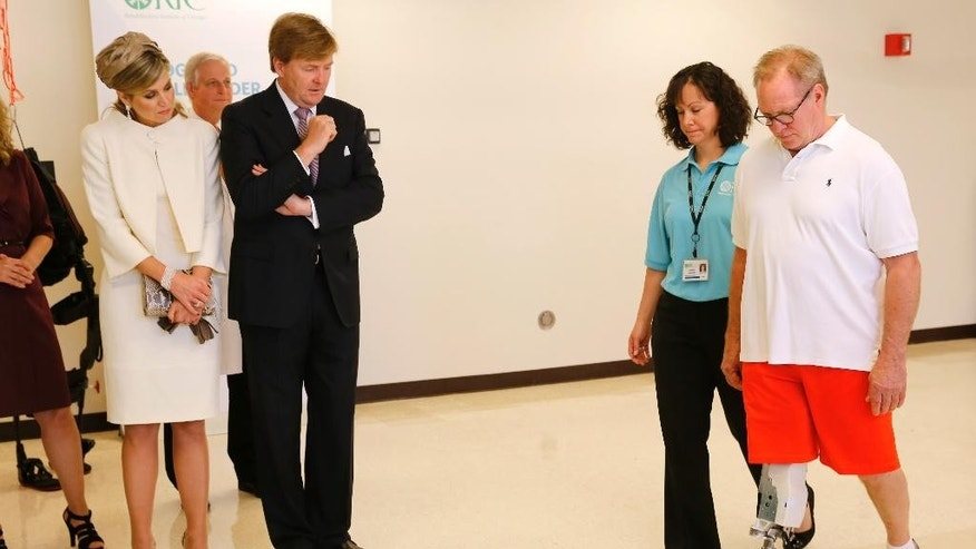 King Willem-Alexander and Queen Maxima of the Netherlands, left, watch Terry Karpowicz, right, and an unidentified staff member at the Rehabilitation Institute of Chicago demonstrate the functions of Karpowicz's robotic leg during a visit by the monarchs Wednesday, June 3, 2015, in Chicago. (AP Photo/Christian K. Lee)