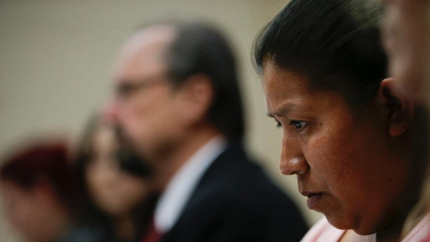 Lorena Rodriguez, right, whose son attended a police-run boot camp, listens to attorney Gregory Owen, background center, during a news conference, Wednesday, June 3, 2015 in Commerce, Calif. Authorities are investigating claims that seven children from Southern California suffered physical abuse while attending the boot camp on the Central Coast. (AP Photo/Jae C. Hong)